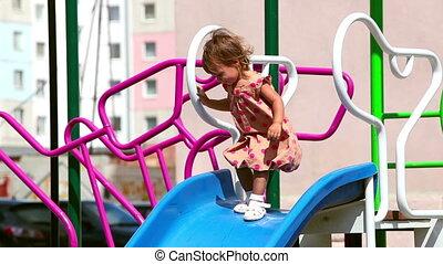 Sliding down the chute - Cheerful child sliding down the...