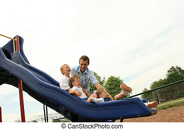 Sliding Fun with Dad - Family of four playing on the sliding...