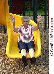 Senior citizen woman with arms upraised on playground sliding board.