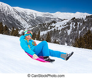 Happy girl sliding down the slope on sled, wearing ski mask, with mountains on background