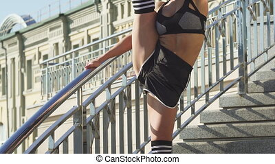 Sliding shot of a sexy female gymnast stretching outdoors on the city streets