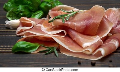 sliced prosciutto or jamon meat on wooden background -...