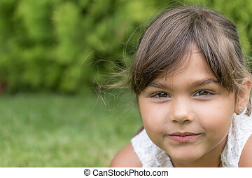 Slightly smiling face of little girl closeup.