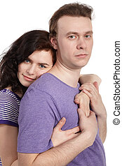 Slightly smiling young woman embraces a serious young man from behind.