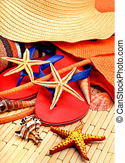 Sliipers, starfish, beach hat, towel on a wood