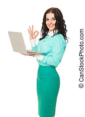 slim beautiful smiling brunette in green skirt and blouse holding laptop over white background