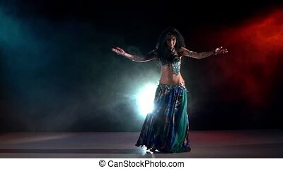 Slim, beautiful woman belly dancer sexy dancing on blue, red, in smoke, slow motion