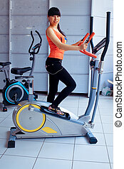 slim beautiful woman exercising on  elliptical trainer