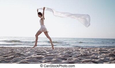 Slim beautiful woman running on sea beach with white silk ...