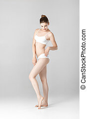 slim beautiful woman with perfect body in white lingerie on gray background