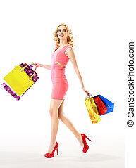 Slim blond woman holding a bunch of paper bags