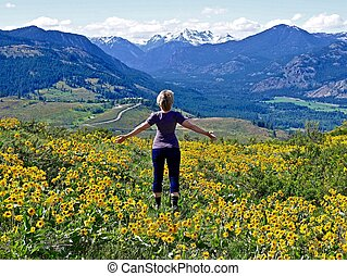 Slim Blond Woman, Yellow Flower, Snow Capped Mountains.