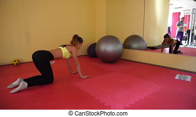 slim blonde sports girl training in a gym