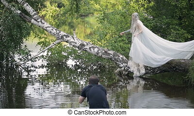 Slim blonde woman stands on birch above water surface. She...