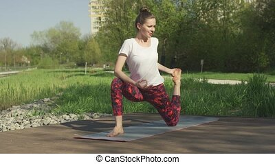 Slim brunette doing yoga twist in park
