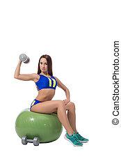 Slim brunette exercising with dumbbells in fitness