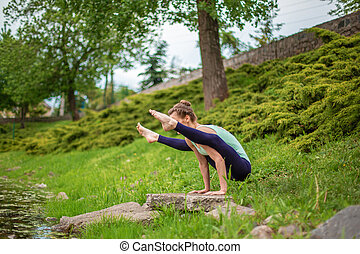 Slim brunette girl doing yoga in the summer on a green lawn by the lake