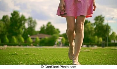 Slim brunette girl in pink dress walks at camera. Slow motion steadicam video