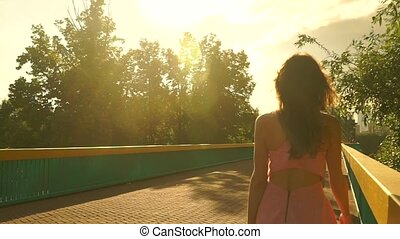 Slim brunette girl in pink dress walks on bridge. Slow motion steadicam clip