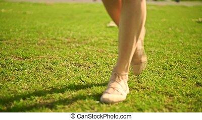 Slim brunette girl in pink dress walks at camera. Slow motion steadicam clip