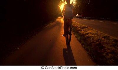 Slim brunette girl riding a bike along summer sunset road. Slow motion tracking shot