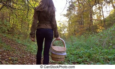 Slim brunette girl walking in autumn forest holding a picnic basket. 4K steadicam video
