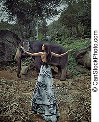 Slim, brunette lady with small elephant