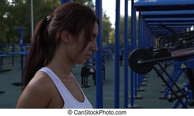 Slim Brunette Woman Exercising in Outdoors Gym.