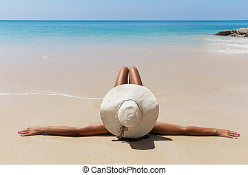 slim brunette woman in hat on beach