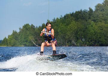 slim brunette woman riding wakeboard on lake