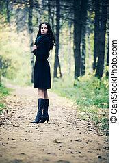 Slim brunette woman walking in a park. Autumn season.