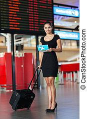 businesswoman standing next to flight information board