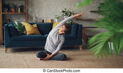 Slim curly-haired girl is doing yoga at home in seated...