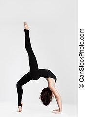 Slim dancer in yoga pose bending over backwards