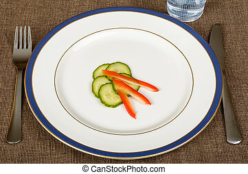A slim dish for dieting made of cucumbers and paprika on white plate. Fork and knife beside.