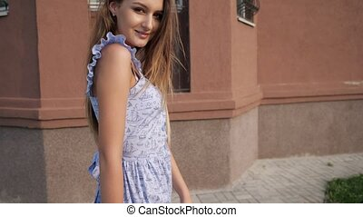 slim long haired model in trendy blue summer dress and beige high heels walks as strutting out onto catwalk along street close-up