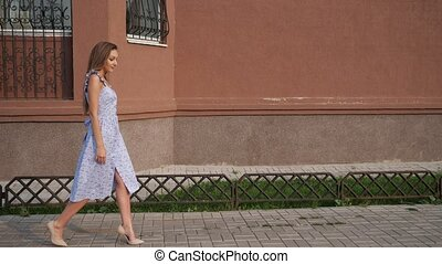 slim long haired model in trendy blue summer dress and beige high heels walks as strutting out onto catwalk along street