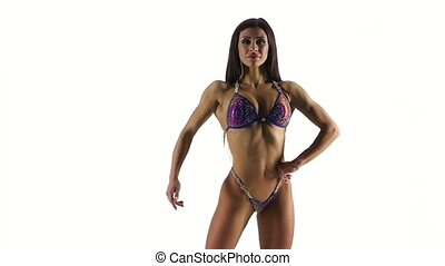 Slim female bodybuilder posing in bikini, fitness competition on white. CLose up. Slow motion.