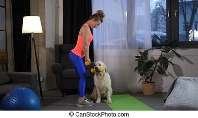 Slim female doing sport exercise with dog trainer