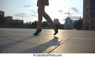 Slim female legs in black shoes on high heels walking on...