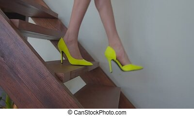 Close-up of beautiful slim female legs in fashionable yellow high heel shoes stepping down wooden stairs slowly and gracefully indoors. Low section of elegant woman in stilettos descending staircase.
