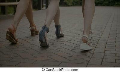 Slim female legs walking on cobblestone sidewalk - Closeup...
