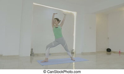 Slim fit beautiful blonde woman practicing medium and advanced difficulty yoga poses inside a bright studio