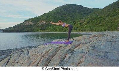 Slim Girl Bends in Yoga Pose on Rock against Ocean