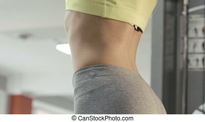 Slim girl doing exercises on horizontal bar in the gym