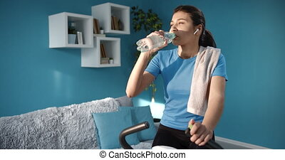 Slim girl drinking water while training on exercise bike