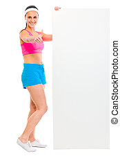 Slim girl holding blank billboard and showing thumbs up