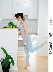 Slim girl in a tracksuit standing on one leg at home, drinks a green smoothie