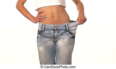 Slim girl in big jeans, showing her lose weight, on white