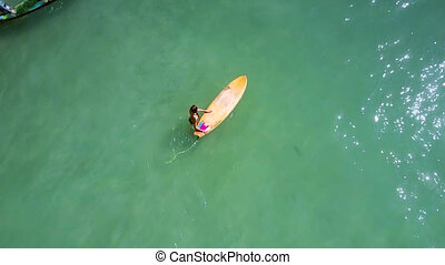 slim girl in bikini lies on surfboard among ocean -...